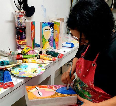 Idit Matan in her studio painting on wooden block